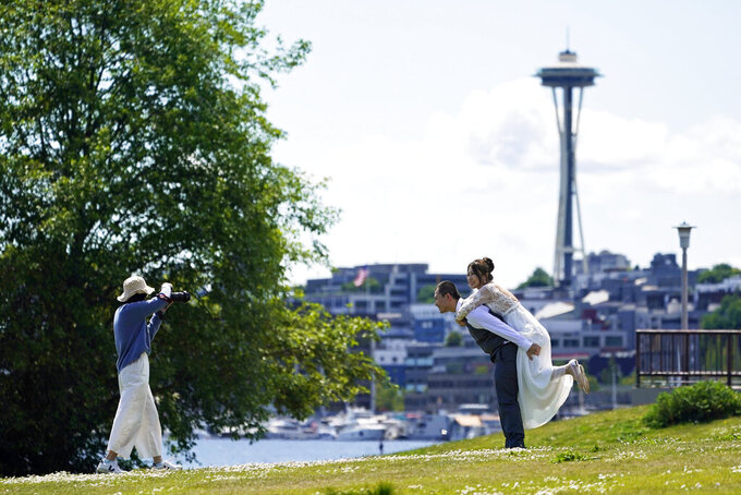 FILE- In this May 10, 2021 file photo, Tom Li, second from right, and his fiancé, Leah Li, right, pose for photos taken by Ella Chang, left, at Gas Works Park in Seattle. The couple, who live in Seattle, are originally from China and have a wedding planned later in the year for September. As COVID-19 cases drop and restrictions ease, many couples are eagerly moving forward with paused wedding plans — or altering existing ones to accommodate more guests. But figuring out where to start and what costs you'll face can still be tricky during this time.  (AP Photo/Ted S. Warren, File)