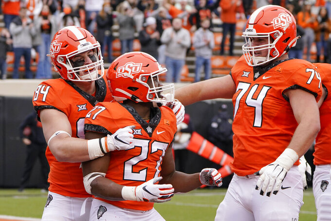 Oklahoma State running back Dezmon Jackson (27) celebrates a touchdown with teammates Dayton Metcalf (84) and Preston Wilson (74) in the first half an NCAA college football game in Stillwater, Okla., Saturday, Nov. 28, 2020. (AP Photo/Sue Ogrocki)