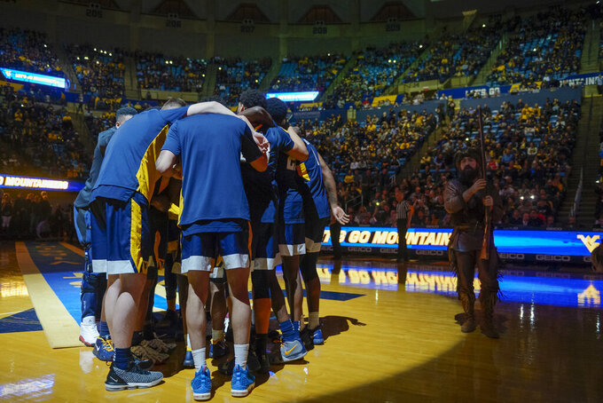 The Mountaineers huddle before an NCAA college basketball game against the University of Texas Longhorns in Morgantown, W.Va. on Saturday Feb. 9, 2019. (AP Photo/Craig Hudson)