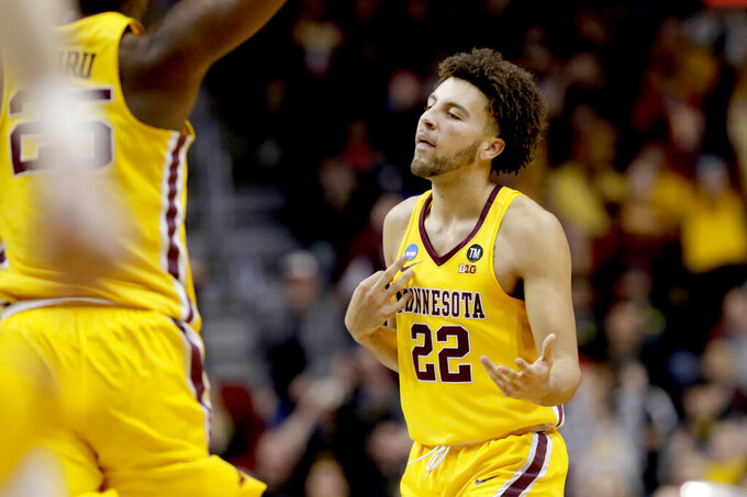 Minnesota's Gabe Kalscheur (22) plays air guitar after scoring a basket against Louisville during the second half of a first round men's college basketball game in the NCAA Tournament, in Des Moines, Iowa, Thursday, March 21, 2019. (AP Photo/Nati Harnik)