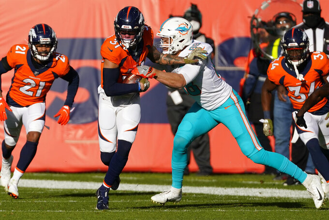 Denver Broncos free safety Justin Simmons is hit by Miami Dolphins tight end Mike Gesicki (88) after an interception during the first half of an NFL football game, Sunday, Nov. 22, 2020, in Denver. (AP Photo/Jack Dempsey)
