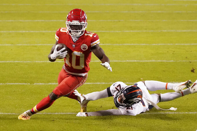 Kansas City Chiefs wide receiver Tyreek Hill (10) avoids Denver Broncos cornerback A.J. Bouye (21) in the first half of an NFL football game in Kansas City, Mo., Sunday, Dec. 6, 2020. (AP Photo/Charlie Riedel)