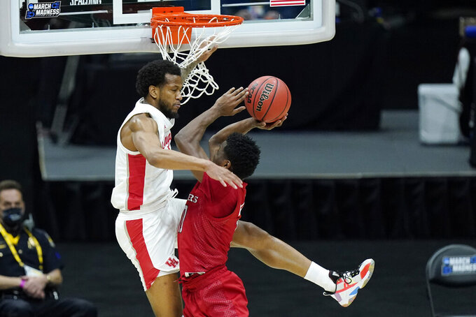 Rutgers' Montez Mathis, right, drives against Houston's Justin Gorham, left, during the first half of a college basketball game in the second round of the NCAA tournament at Lucas Oil Stadium in Indianapolis Sunday, March 21, 2021. (AP Photo/Mark Humphrey)