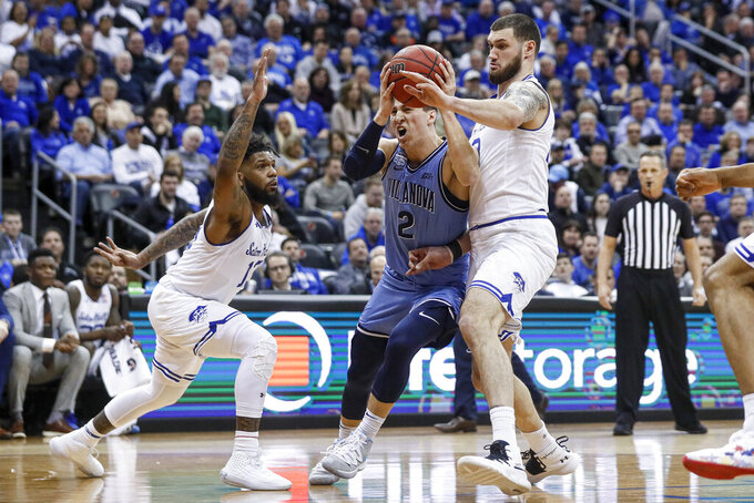 Villanova's Collin Gillespie (2) drives against Seton Hall's Sandro Mamukelashvili, right, and Seton Hall's Myles Powell, left, during the first half of an NCAA college basketball game, Wednesday, March 4, 2020, in Newark, N.J. (AP Photo/John Minchillo)