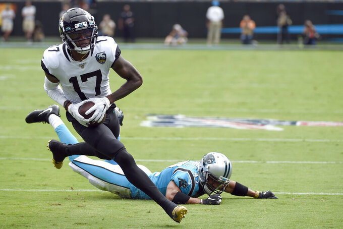 Jacksonville Jaguars wide receiver D.J. Chark (17) runs for a touchdown while Carolina Panthers defensive back Ross Cockrell (47) misses the tackle during the first half of an NFL football game in Charlotte, N.C., Sunday, Oct. 6, 2019. (AP Photo/Mike McCarn)