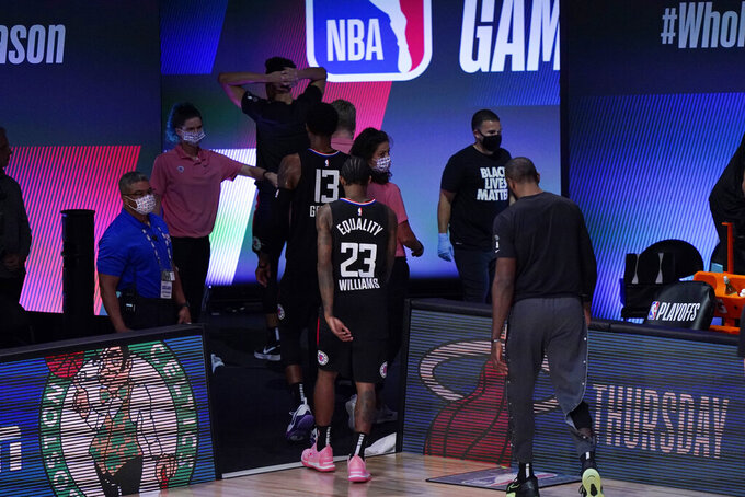 Los Angeles Clippers players walk off of the court following their loss to the Denver Nuggets in an NBA conference semifinal playoff basketball game Tuesday, Sept. 15, 2020, in Lake Buena Vista, Fla. (AP Photo/Mark J. Terrill)
