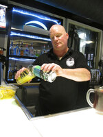 Bartender Rodney Shipp pours a can of