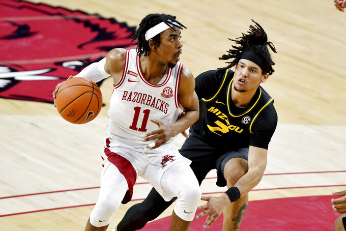 Arkansas guard Jalen Tate (11) tries to get past Missouri defender Torrence Watson (2) during the second half of an NCAA college basketball game in Fayetteville, Ark., Saturday, Jan. 2, 2021. (AP Photo/Michael Woods)