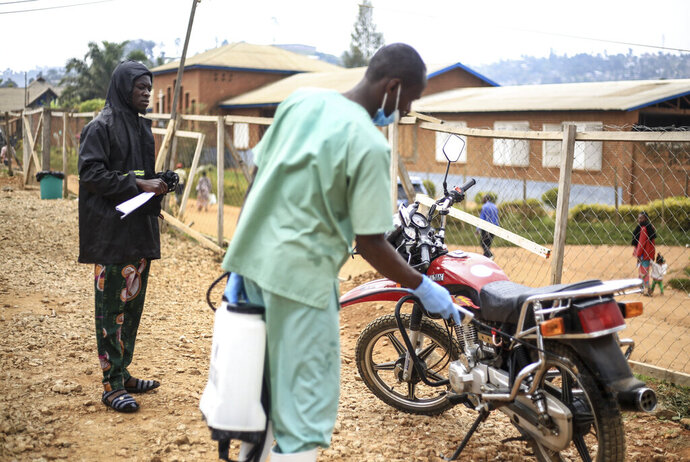 Health workers decontaminate the motorbike of Germain Kalubenge, left, upon his arrival after transporting a suspected Ebola case to an Ebola transit center where potential cases are evaluated, in Beni, Congo, Thursday, Aug. 22, 2019. Kalubenge is a rare motorcycle taxi driver who is also an Ebola survivor in eastern Congo, making him a welcome collaborator for health workers who have faced deep community mistrust during the second deadliest Ebola outbreak in history. (AP Photo/Al-hadji Kudra Maliro)