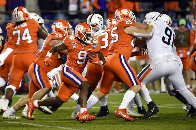 Clemson running back Travis Etienne (9) runs the ball against Virginia during the first half of the Atlantic Coast Conference championship NCAA college football game in Charlotte, N.C., Saturday, Dec. 7, 2019. (AP Photo/Mike McCarn)