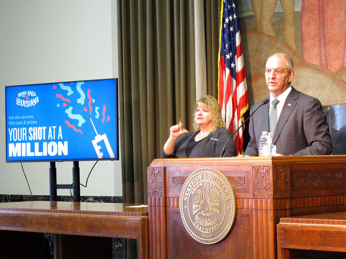 Louisiana Gov. John Bel Edwards recommends that his state's residents return to wearing masks indoors, whether they are vaccinated against COVID-19 or not, if they are unable to distance from people, Friday, July 23, 2021, in Baton Rouge, La. Edwards speaks next to a sign promoting the state's coronavirus vaccine lottery. (AP Photo/Melinda Deslatte)