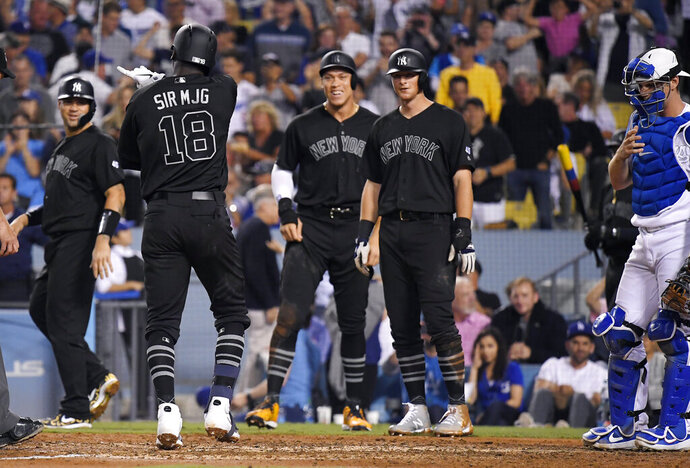 New York Yankees' Didi Gregorius, second from left, scores after hitting a grand slam as Gary Sanchez, left, Aaron Judge, center, and DJ LeMahieu wait for him as Los Angeles Dodgers catcher Will Smith stands nearby during the fifth inning of a baseball game Friday, Aug. 23, 2019, in Los Angeles. (AP Photo/Mark J. Terrill)