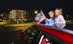 Myers, 5, left, and Tatum Mantooth, 8, wave an American flag and pompoms in support of healthcare workers from the sunroof of their car during a healthcare rally in the parking lot at Owensboro Health Regional Hospital in Owensboro, Ky., Tuesday, Nov. 24, 2020. (Alan Warren/The Messenger-Inquirer via AP)