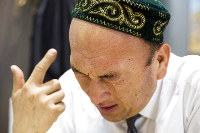 In this March 29, 2018, photo, Omir Bekali cries as he details the psychological stress endured while in a Chinese internment camp during an interview in Almaty, Kazakhstan. Since 2016, Chinese authorities in the heavily Muslim region of Xinjiang have ensnared tens, possibly hundreds of thousands of Muslim Chinese, and even foreign citizens, in mass internment camps. The program aims to rewire detainees' thinking and reshape their identities. Chinese officials say ideological changes are needed to fight Islamic extremism. (AP Photo/Ng Han Guan)