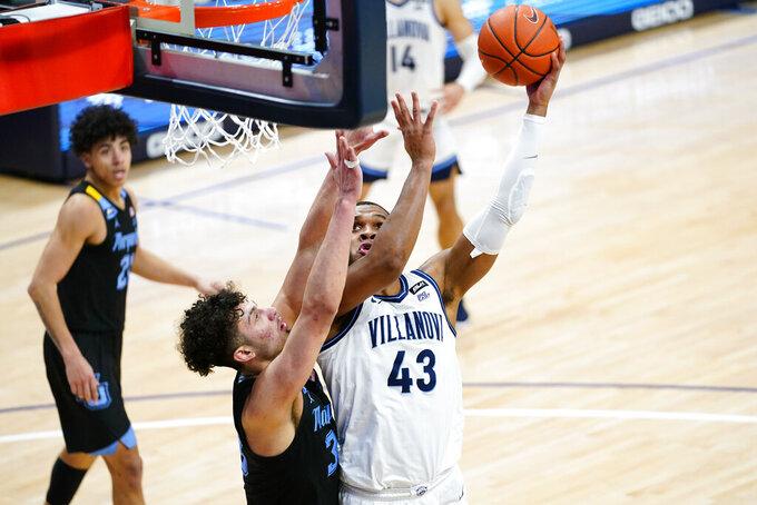 Villanova's Eric Dixon (43) goes up for a shot against Marquette's Dawson Garcia (33) during the second half of an NCAA college basketball game, Wednesday, Feb. 10, 2021, in Villanova, Pa. (AP Photo/Matt Slocum)