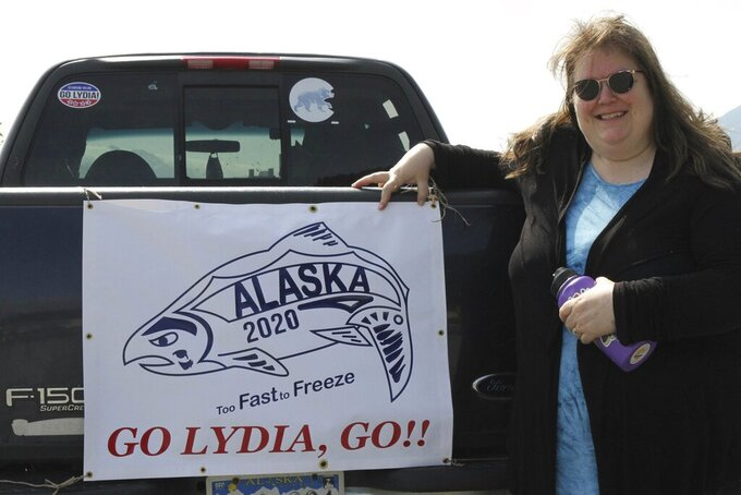 Sarah Spanos displays signs of support for Olympic swimmer Lydia Jacoby adorning her pickup truck, in Seward, Alaska, Tuesday, July 27, 2021. Jacoby, a 17-year-old from Seward, scored a major upset when the first Alaskan ever on the U.S. Olympics swimming team won the gold medal in the 100-meter breaststroke at the Tokyo Games. (AP Photo/Mark Thiessen)
