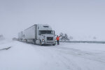 Frank Van Buren, the manager of a travel center, gives direction to semi-truck drivers who are pulling off Interstate 40 in Bellemont, Arizona, on Thursday, Feb. 21, 2019. Feb. 21, 2019. Schools across northern Arizona canceled classes and some government offices decided to close amid a winter storm that's expected to dump heavy snow in the region. (AP Photo/Felicia Fonseca)