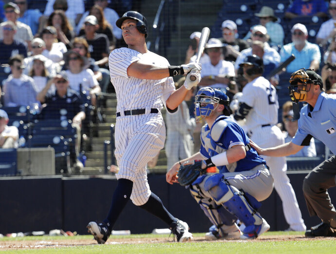 New York Yankees' Aaron Judge, left, follows through on a double in the third inning during a spring training baseball game against the Toronto Blue Jays, Monday, Feb. 25, 2019, in Tampa, Fla. At right is Toronto Blue Jays catcher Danny Jansen. (AP Photo/Lynne Sladky)
