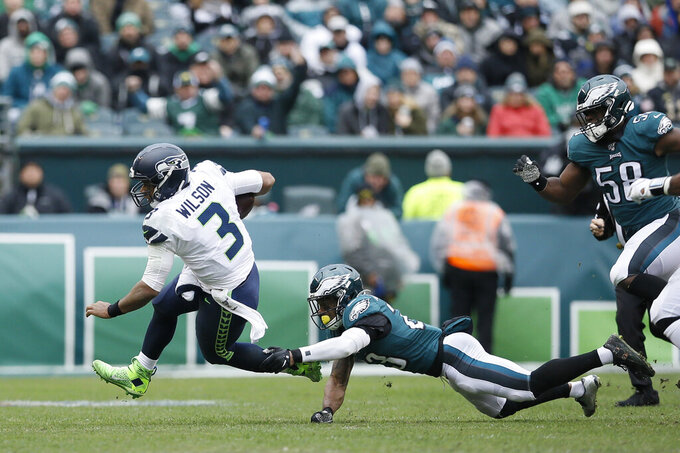 Seattle Seahawks' Russell Wilson, left, tries to avoid Philadelphia Eagles' Rodney McLeod during the first half of an NFL football game, Sunday, Nov. 24, 2019, in Philadelphia. (AP Photo/Michael Perez)