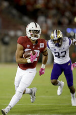 Stanford's Cameron Scarlett, left, runs past Washington's Keith Taylor (27) during the first half of an NCAA college football game Saturday, Oct. 5, 2019, in Stanford, Calif. (AP Photo/Ben Margot)