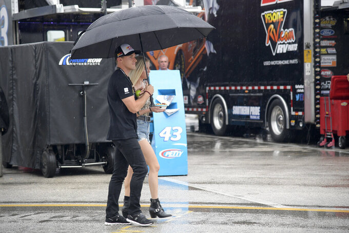 Driver Parker Kligerman, left, walks through the garage area during a rain delay before a NASCAR Cup Series auto race at Daytona International Speedway, Saturday, July 6, 2019, in Daytona Beach, Fla. (AP Photo/Phelan M. Ebenhack)