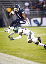 Connecticut running back Art Thompkins (1) leaps over Wagner defensive back Naseem Barnett (33) during the first half of an NCAA college football game Thursday, Aug. 29, 2019, in East Hartford, Conn. (AP Photo/Stephen Dunn)