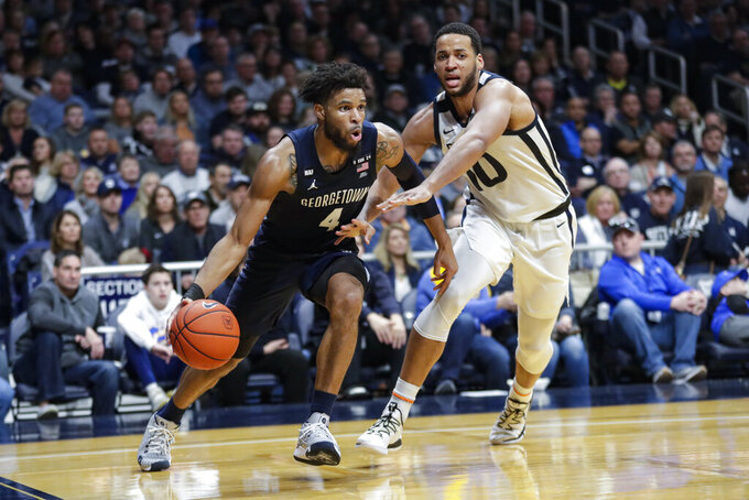 Georgetown guard Jagan Mosely (4) drive son Butler forward Bryce Nze (10) in the second half of an NCAA college basketball game in Indianapolis, Saturday, Feb. 15, 2020. Georgetown defeated Butler 73-66. (AP Photo/Michael Conroy)