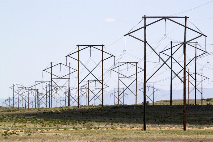 FILE - This May 20, 2012, file photo, shows one of the major transmission lines that runs to the west of Albuquerque, N.M. The parent company of New Mexico's largest electric utility will become part of energy giant Iberdrola's global holdings under a multibillion-dollar merger.  Under the agreement announced Wednesday, Oct. 21, 2020, Iberdrola's majority-owned U.S. subsidiary Avangrid will acquire PNM Resources and its assets in New Mexico and Texas. The merger will require approval from a number of state and federal regulators in a process that's expected to take the next 12 months. (AP Photo/Susan Montoya Bryan, File)