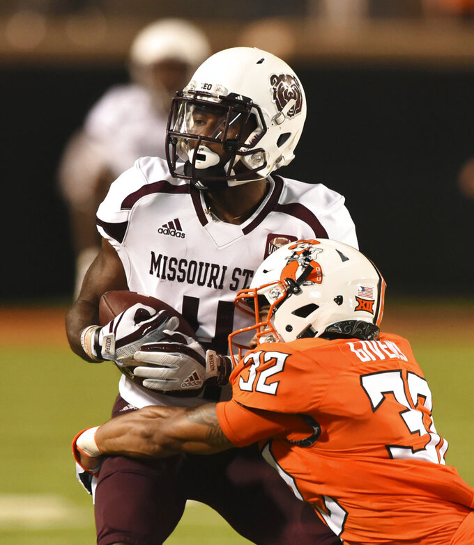 Missouri State's Matt Rush is wrapped up by Oklahoma State's Malik Givens during the second half of an NCAA college football game in Stillwater, Okla., Thursday, Aug. 30, 2018. (AP Photo/Brody Schmidt)