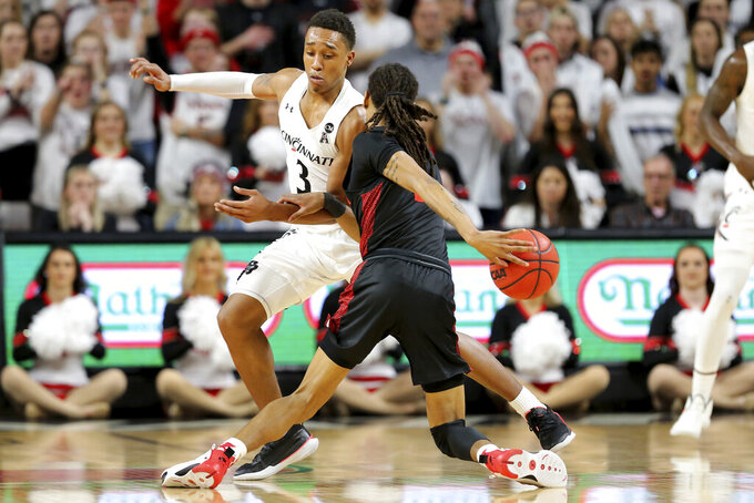 Houston guard Caleb Mills (2) goes around the back as Cincinnati guard Mika Adams-Woods (3) defends in the first half in the first half of an NCAA college basketball game, Saturday, Feb. 1, 2020, in Cincinnati. (Kareem Elgazzar/The Cincinnati Enquirer via AP)