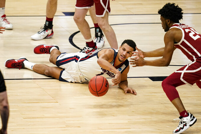 Gonzaga guard Jalen Suggs (1) goes for a loose ball in front of Oklahoma guard Elijah Harkless (24) in the first half of a second-round game in the NCAA men's college basketball tournament at Hinkle Fieldhouse in Indianapolis, Monday, March 22, 2021. (AP Photo/Michael Conroy)