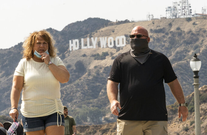 Visitors wear face masks outdoors at the Griffith Observatory in Los Angeles, Monday, May 17, 2021. California is keeping its rules for wearing face masks in place until the state more broadly lifts its pandemic restrictions on June 15. (AP Photo/Damian Dovarganes)