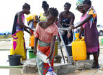 A young girl fetches water at a camp for displaced survivors of cyclone Idai in Beira, Mozambique, Tuesday, April, 2, 2019. Mozambican and international health workers raced Monday to contain a cholera outbreak in the cyclone-hit city of Beira and surrounding areas, where the number of cases has jumped to more than 1,000.  (AP Photo/Tsvangirayi Mukwazhi)