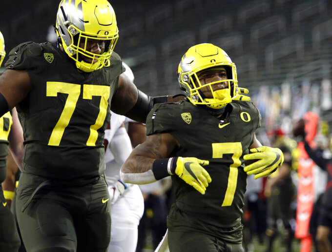 Oregon's CJ Verdell, right, celebrates a first-quarter touchdown with teammate George Moore during an NCAA college football game against Stanford, Saturday, Nov. 7, 2020, in Eugene, Ore. (AP Photo/Chris Pietsch)