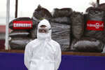 A police wearing a personal protective equipment stands in front of seized illegal drugs before being burnt during a destruction ceremony to mark International Day against Drug Abuse and Illicit Trafficking outside Yangon, Myanmar, Friday, June 26, 2020. More than $839 million of seized illegal drugs were destroyed in the country on Friday, officials said. Myanmar has long been a major source of illegal drugs for East and Southeast Asia, despite repeated efforts to crack down. (AP Photo/Thein Zaw)
