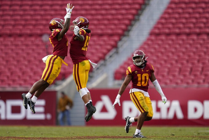 Southern California safeties Max Williams (4) and Talanoa Hufanga (15), and linebacker Ralen Goforth (10) celebrate after an incomplete pass intended for Arizona State wide receiver LV Bunkley-Shelton during the second half of an NCAA college football game Saturday, Nov. 7, 2020, in Los Angeles. (AP Photo/Ashley Landis)