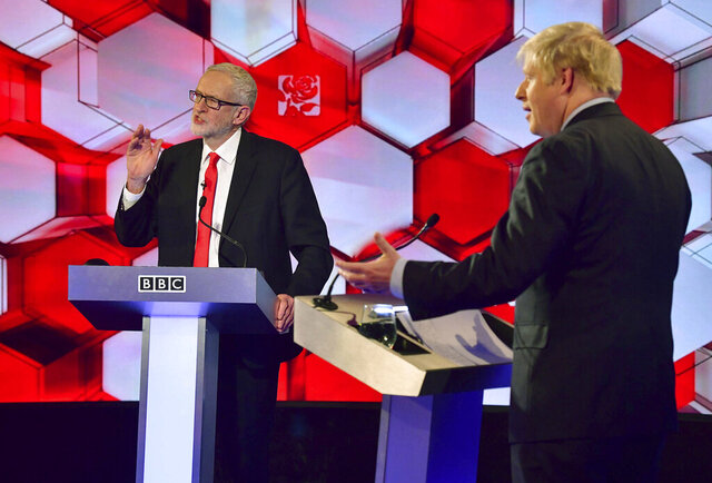 Opposition Labour Party leader Jeremy Corbyn, left, and Britain's Prime Minister Boris Johnson, during a head to head live Election Debate at the BBC TV studios in Maidstone, England, Friday Dec. 6, 2019.  Britain's Brexit is one of the main issues for political parties and for voters, as the UK prepares for a General Election on Dec. 12.  The debate is moderated by TV presenter Nick Robinson, right. ( Jeff Overs/BBC via AP)