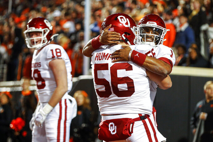 Oklahoma tight end Austin Stogner (18) yells in celebration while offensive lineman Creed Humphrey (56) hugs quarterback Jalen Hurts (1) after Hurts' touchdown catch against Oklahoma State during an NCAA college football game, Saturday, Nov. 30, 2019, in Stillwater, Okla. (Ian Maule/Tulsa World via AP)