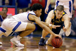 Kansas' Devon Dotson, left, and West Virginia's Sean McNeil chase the ball during the second half of an NCAA college basketball game Saturday, Jan. 4, 2020, in Lawrence, Kan. (AP Photo/Charlie Riedel)