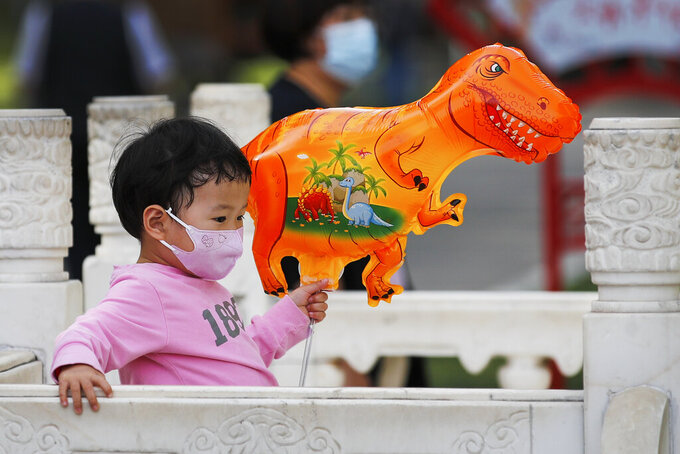 A child wearing a face mask to help curb the spread of the coronavirus holds a dinosaur shaped balloon walks at a public park in Beijing, Sunday, May 16, 2021. (AP Photo/Andy Wong)