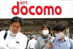 Passers-by walk past a NTT DoCoMo shop in Tokyo, Tuesday, Sept. 29, 2020. Shares in Japanese telecoms giant Nippon Telegraph & Telephone, or NTT, fell Tuesday on news it is preparing for a takeover of its mobile phone carrier NTT DoCoMo. (Kyodo News via AP)