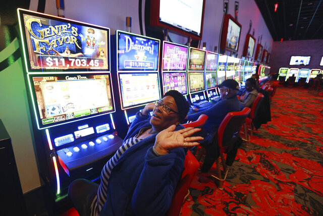 In this Dec. 16, 2019 photo, Shelia Hargrove, of Richmond, plays gaming machines at Rosie's gaming center in Richmond, Va.  Gambling-related issues are set to be one of the hottest topics at the state Capitol when lawmakers return to the Richmond next month to kick off the 2020 legislative session. Lawmakers will decide whether to legalize online sports betting and whether to regulate betting machines that have proliferated in convenience stores in recent years. (AP Photo/Steve Helber)