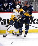 Winnipeg Jets' Jack Roslovic (28) is checked by Nashville Predators' Roman Josi (59) during first period NHL hockey action in Winnipeg, Manitoba, Sunday Jan. 12, 2020. (Fred Greenslade/The Canadian Press via AP)