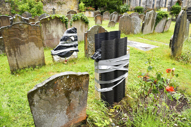 The damaged headstone and footstone on the grave of an enslaved African man, in St Mary's churchyard, in Bristol, England, Thursday June 18, 2020, which have been vandalised in an apparent
