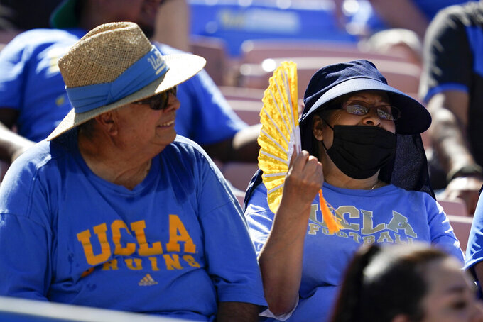 One fan wearing a face mask and one without sit in the stands during an NCAA college football game between Hawaii and UCLA, Saturday, Aug. 28, 2021, in Pasadena, Calif. College football fans headed back into stadiums Saturday, some of them for the first time in two years. (AP Photo/Ashley Landis)