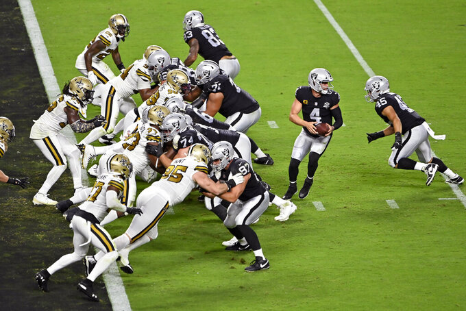 Las Vegas Raiders quarterback Derek Carr (4) prepares to hand off the ball against the New Orleans Saints during the second half of an NFL football game, Monday, Sept. 21, 2020, in Las Vegas. (AP Photo/David Becker)