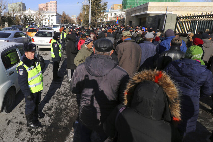 Police watch as protestors gather outside the Government Palace in Ulaanbaatar, Mongolia, Friday, Nov. 15, 2019. Mongolian political fringe groups protested in the capital, Ulaanbaatar, on Friday to demand the dissolution of parliament as economic woes continue to grip the country. (AP Photo/Ganbat Namjilsangarav)