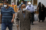 People wearing protective face masks to help prevent the spread of the coronavirus walk on a sidewalk in the city of Zanjan, some 330 kilometers (205 miles) west of the capital Tehran, Iran, Sunday, July 5, 2020. Iran on Sunday instituted mandatory mask-wearing as fears mount over newly spiking reported deaths from the coronavirus, even as its public increasingly shrugs off the danger of the COVID-19 illness it causes. (AP Photo/ Vahid Salemi)