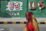 An Indian woman looks at a wall painted with portraits of U.S. President Donald Trump and Indian Prime Minister Narendra Modi ahead of Trump's visit, in Ahmadabad, India, Tuesday, Feb. 18, 2020. Trump is scheduled to visit the city during his Feb. 24-25 India trip. (AP Photo/Ajit Solanki)