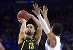 Oregon forward Paul White, left, shoots as UCLA guard Jaylen Hands defends during the first half of an NCAA college basketball game Saturday, Feb. 23, 2019, in Los Angeles. (AP Photo/Mark J. Terrill)